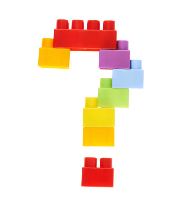 Question mark made of colorful plastic toy construction bricks, isolated over the white background